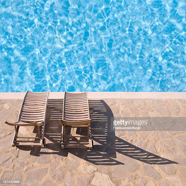 Two wooden deckchairs at the edge of a swimming pool