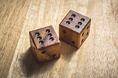 Two wooden dice with the number 6 on a table