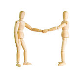 Two wooden figure dolls doing a handshake over a white background