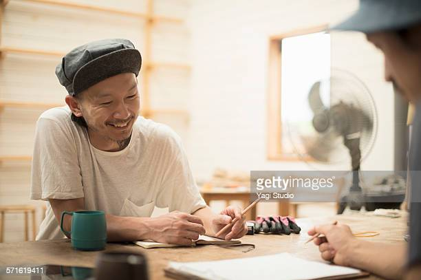 Two woodworkers meeting in carpentry workshop