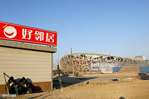 Two workers are enjoying the sunshine on the construction site of the Bird's Nest Beijing's National Stadium which will host the Opening and Closing...