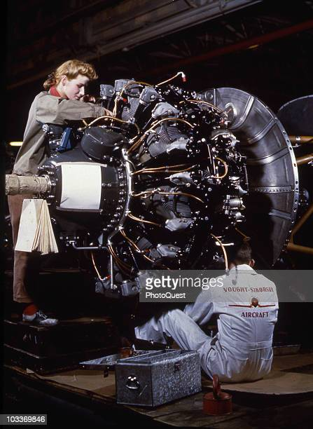 Two workers at the Vought Sikorski Aircraft factory assemble a Pratt Whitney R2800 engine the type used in the Vought F4U 'Corsair' sighter aircraft...