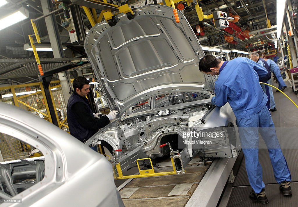 Two workers attach the hood to the car body on the BMW 3-series production line at the BMW factory on March 15, 2010 in Munich, Germany. The German car maker will present the company's business report for 2009 on Wednesday.