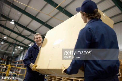 Two workers carrying large box : Stock Photo