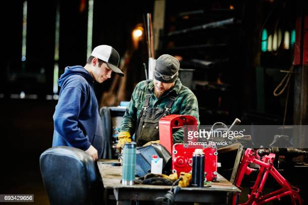 Two workers discussing project in metal workshop