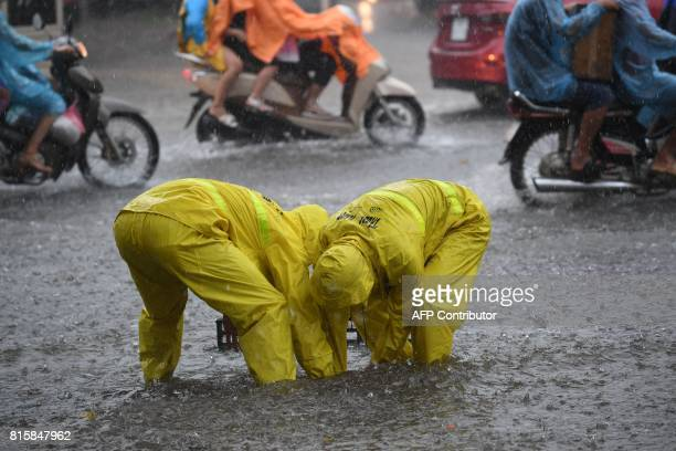 Two workers from the municipal drainage company open a sewer on a flooded street in Hanoi on July 17 after tropical storm Talas made landfall in...