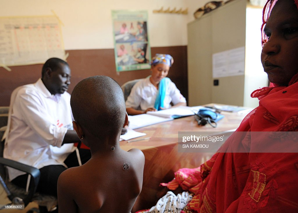 Two workers (back)from the NGO Doctors Without Borders speak with a sick chaild in Gao, in the north of Mali, on February 4, 2013. Schools reopened today in Gao after the town was taken on January 26 by French and Malian forces from Islamists who had been occupying it for the last year.