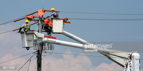 Two workers in a crane repairing a power pole