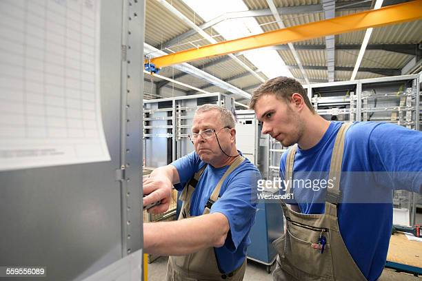 Two workers in a switchboard construction factory