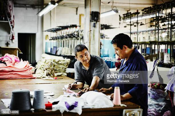 Two workers in discussion at workbench in factory