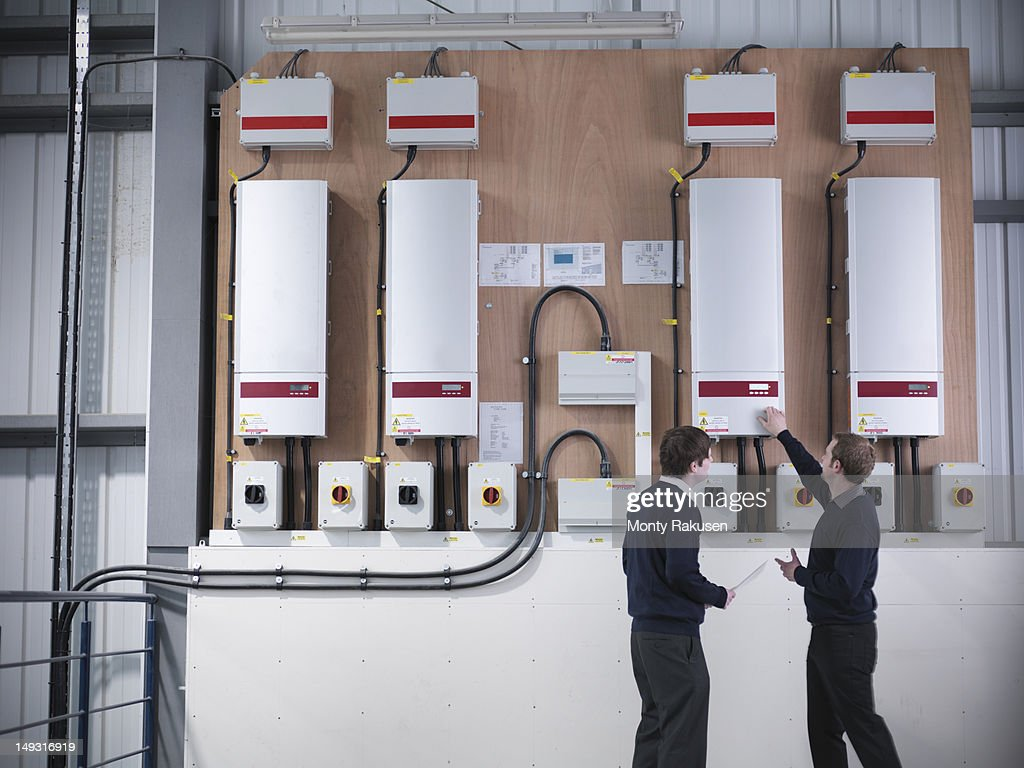 Two workers inspecting industrial solar panel controls