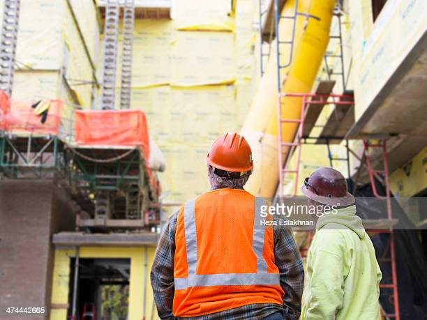 Two workers look at construction site