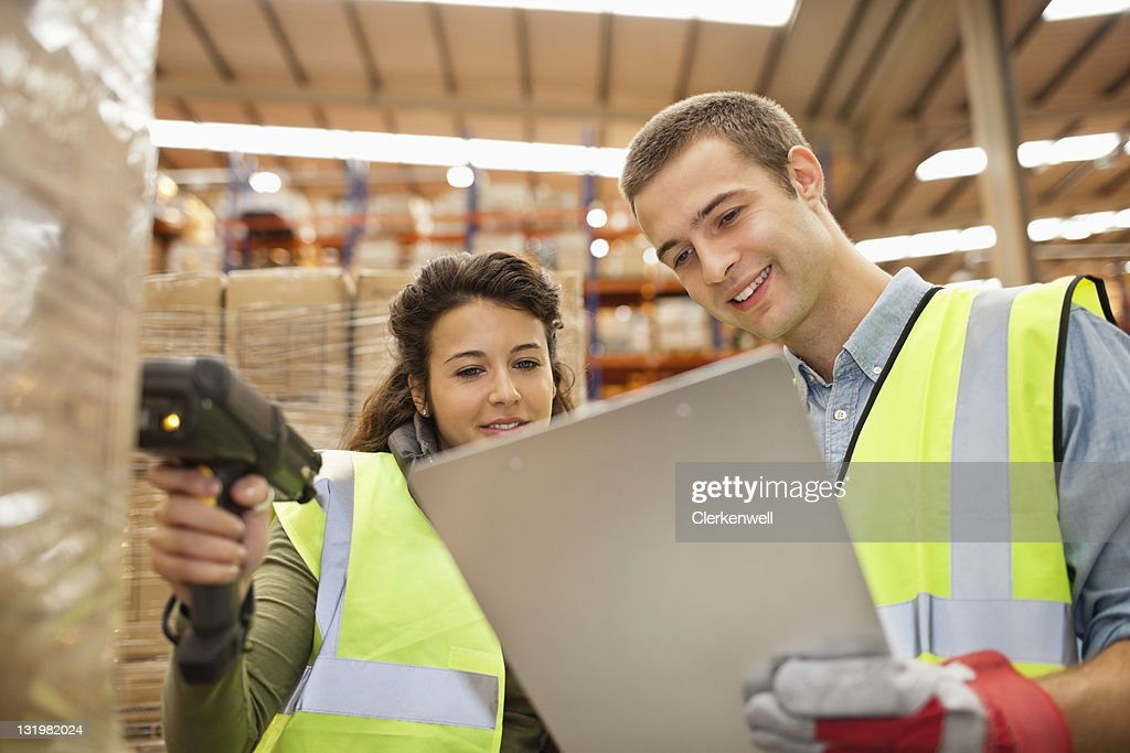 Two workers looking at checklist while scanning barcodes on cardboard boxes : Stock Photo