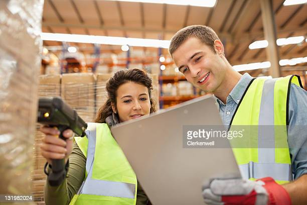 Two workers looking at checklist while scanning barcodes on cardboard boxes