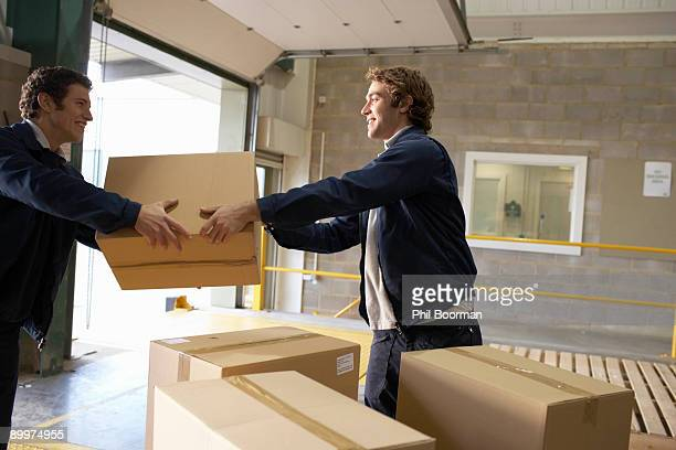 Two workers passing box