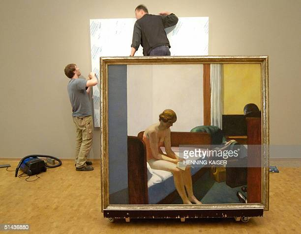 Two workers prepare the hangingup of the painting 'Hotel Room' of USartist Edward Hopper at the Museum Ludwig in Cologne 07 October 2004 The museum...
