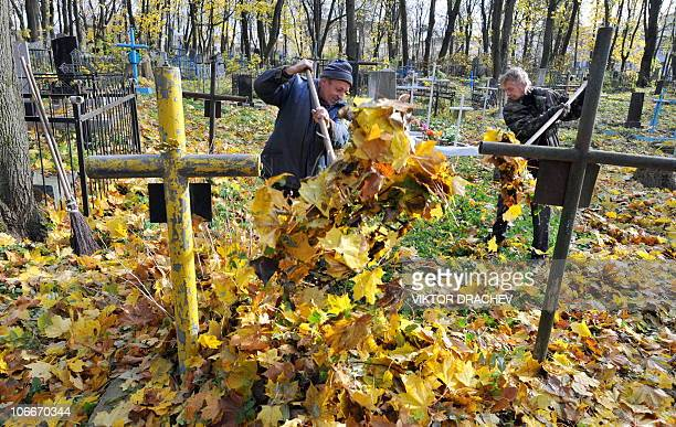 Two workers rake up fallen leaves at a cemetery as they prepare for the parental Saturday church holiday in Minsk on October 27 2010 The Organization...