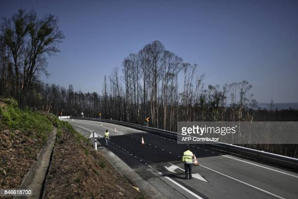 Two workers repair the pavement of the N236 road in Pedrogao Grande on August 9 where 47 people were killed while trying to escape a wildfire that...