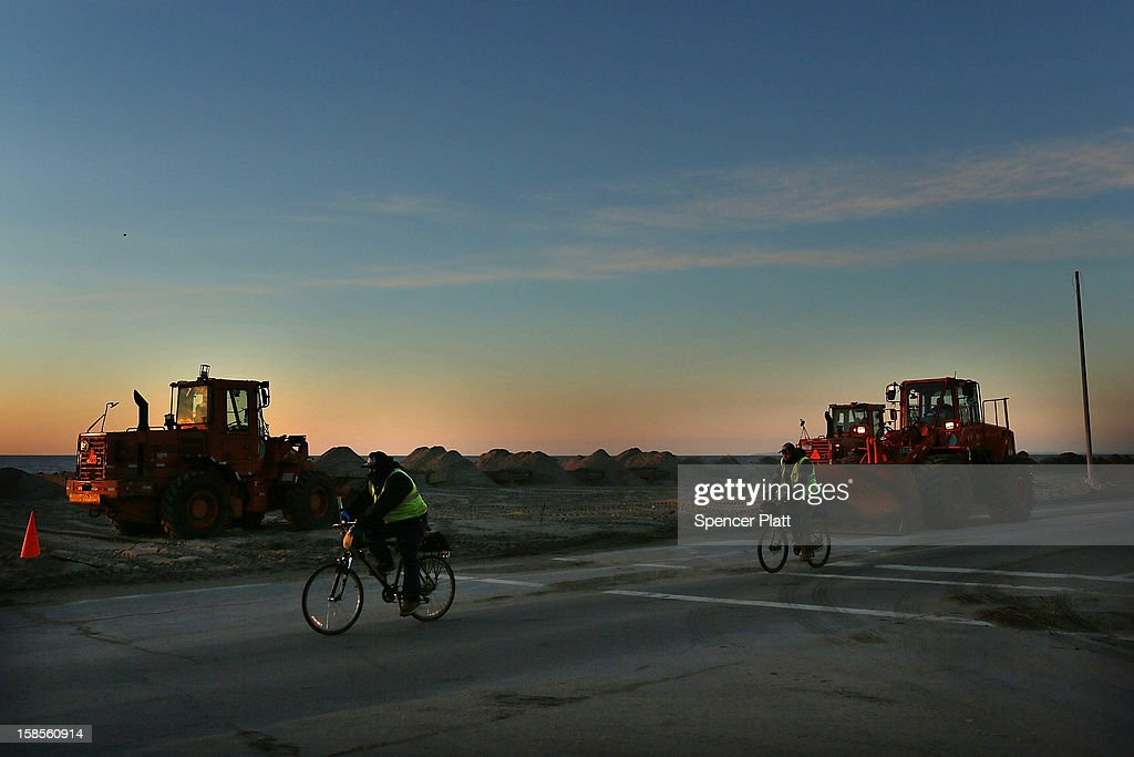 Two workers ride their bikes down the road at dawn near the heavily damaged boardwalk in the Rockaway neighborhood on November 19, 2012 in the Queens borough of New York City. As the holidays approach after Superstorm Sandy slammed into parts of New York and New Jersey, thousands of residents and businesses are still recovering from the devastation.