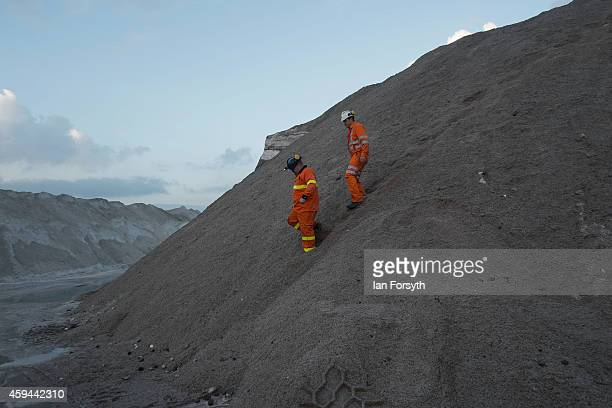 Two workers walk down after inspecting a pile of salt product at the potash facility at Tees Docks on November 20 2014 in Tees Docks United Kingdom...