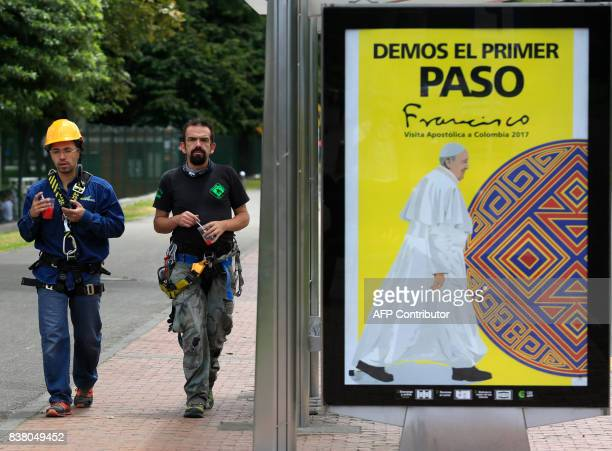 Two workers walks past a sign reading 'Let's all take the first step' ahead of Pope Francis' upcoming visit in Bogota on August 23 2017 Pope Francis...