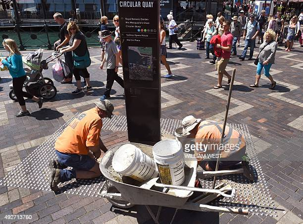 Two workman lay bricks as tourists pass by in Sydney's Circular Quay on October 15 as Australia's unemployment rate remained stable at 62 percent in...