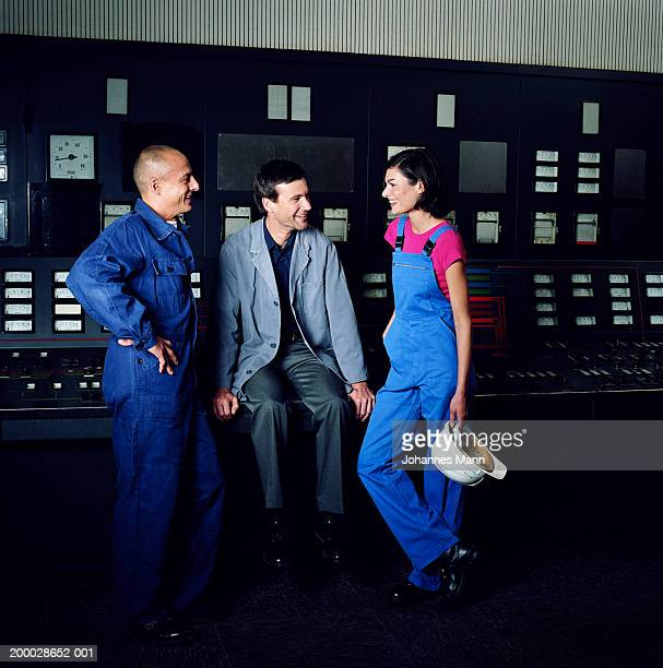 Two workmen and woman relaxing by control panel in power station