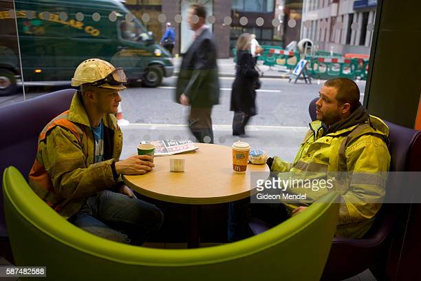 Two workmen enjoy the new trendy coffee bar style ambience and design at the Cannon Street branch of McDonalds in the City of London This is one of...
