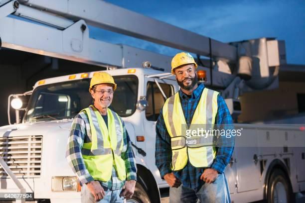Twee werklieden in veiligheidsvesten met vrachtwagen