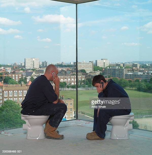Two workmen sitting on unplumbed toilet bowls using mobile phones