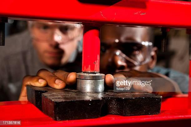 Zwei Arbeiter werden sichtbar sein über eine hydraulisch Drücken Sie in der Werkstatt