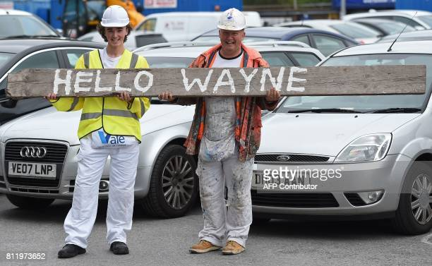 Two workmen welcome Everton's new signing English striker Wayne Rooney outside Goodison Park in Liverpool on July 10 following his move to Everton...