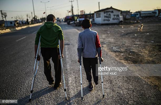 Two wounded friends Muhammed from Aleppo and Ahmed from Idlib in Syria walk in the refugee camp near the Oncupinar crossing gate in Kilis in...