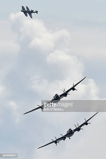 Two WWII Lancaster bombers a Hurricane and a Spitfire perform a battle of Britain flypast during the Eastbourne airshow 'Airbourne' off the coast at...