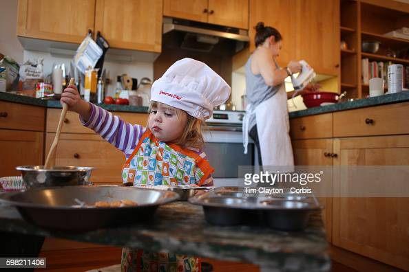 a two year old girl cooking with her mum in the kitchen. Black Bedroom Furniture Sets. Home Design Ideas