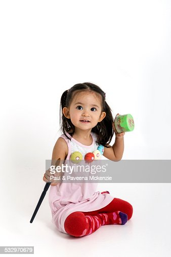 Two year old girl, holding paint brush and paint