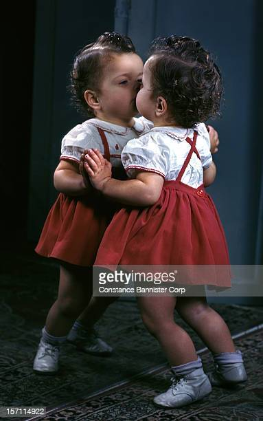 Two year old girl kissing her reflection in mirror 7th April 1957