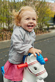 two year old girl playing on rocking horse