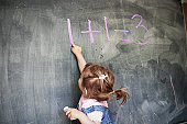 Two year old girl pointing at a blackboard