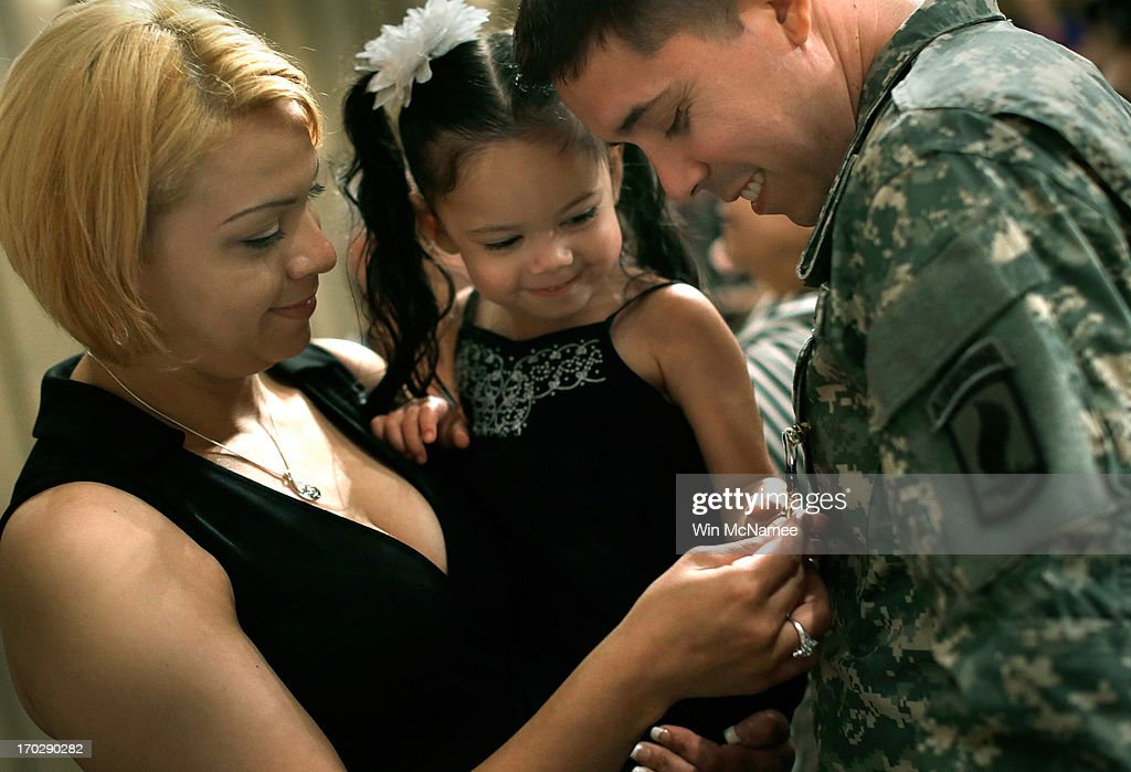 Two year old Yoselin Lopez (C), held by her mother Jennifer Lopez (L), inspects a Purple Heart awarded to her father, U.S. Army Specialist Arael Lopez-Lopez (R), following a Purple Heart ceremony at Mount Vernon June 10, 2013 in Mount Vernon, Virginia. The U.S. Army celebrated its 238th birthday at the home of George Washington with a ceremony that included the awarding of the Purple Heart for three soldiers wounded in Afghanistan. Lopez received his injuries from an RPG explosion followed by a dismounted IED in Wardak Province on August 8, 2012.