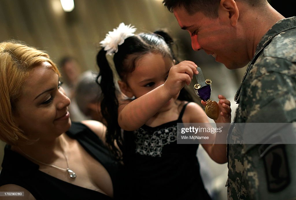 Two year old Yoselin Lopez (C), held by her mother Jennifer Lopez (L), pins a Purple Heart on her father, U.S. Army Specialist Arael Lopez-Lopez (R), following a Purple Heart ceremony at Mount Vernon June 10, 2013 in Mount Vernon, Virginia. The U.S. Army celebrated its 238th birthday at the home of George Washington with a ceremony that included the awarding of the Purple Heart for three soldiers wounded in Afghanistan. Lopez received his injuries from an RPG explosion followed by a dismounted IED in Wardak Province on August 8, 2012.