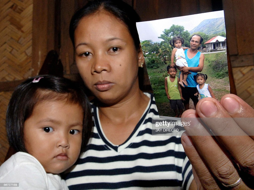 WITH 'PHILIPPINESUNRESTCOMMUNISTRIGHTS' Two yearold Menchie Nuqui joined by her 33yearold mother Ligaya Nuqui displays a picture 10 January 2006 of...