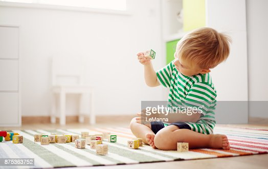 two years old child sitting on the floor with wooden cubes : Stock Photo
