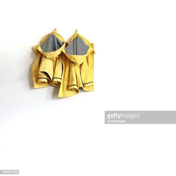 Two yellow raincoats hanging on wall
