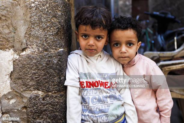 Two Yemeni children pose for a picture in a market in the capital Sanaa on January 24 2017 The devastating conflict that escalated in March 2015 with...
