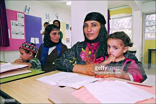 Two Yemeni Jewish women Varda and Jamila hold their respective child 14 July 1993 as they study Hebrew in the classroom of an immigrant absorption...