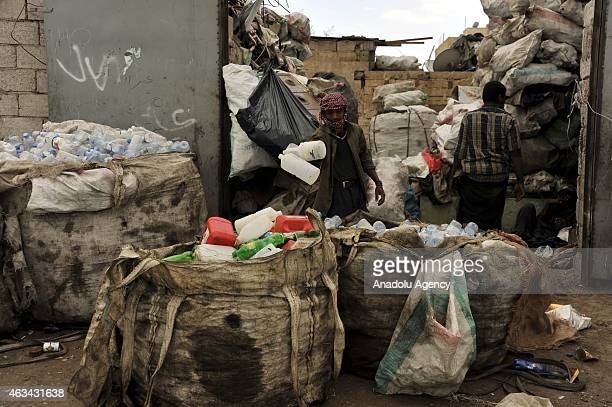 Two Yemeni man collect garbages to recycle to earn money are seen inside dumps in Sanaa Yemen on February 14 2015 UNICEF had announced that 147...