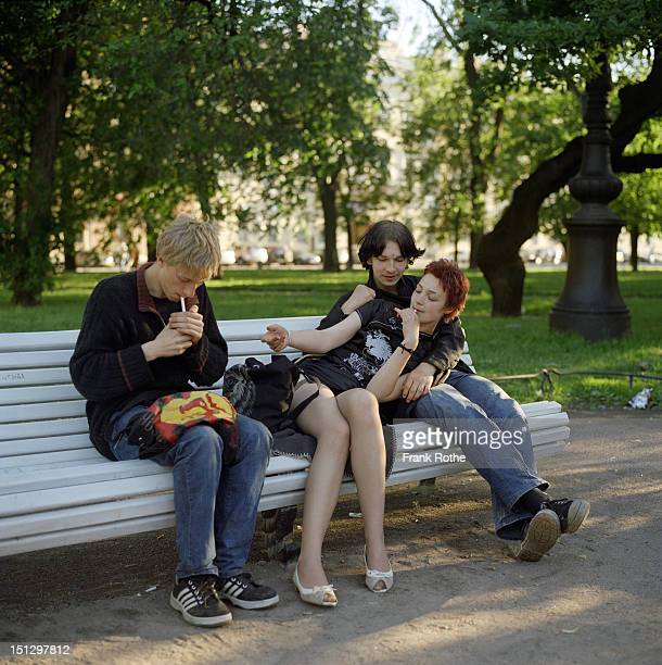 two you man with a female smoking on a bench