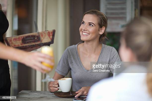 Two young adult female friends ordering from menu in cafe