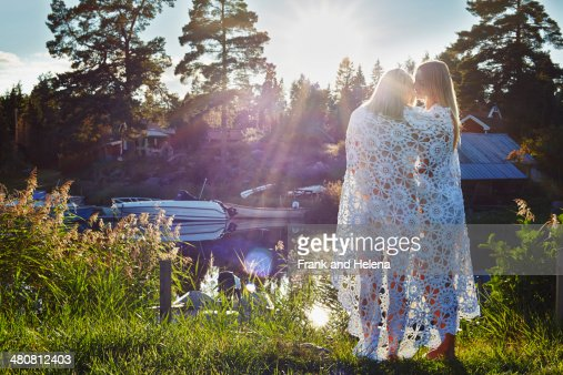 Two young adult female friends wrapped in blanket, Gavle, Sweden